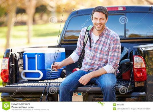 man-sitting-pick-up-truck-camping-holiday-wearing-rucksack-smiling-38632895