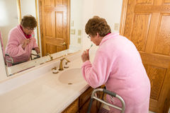 elderly-senior-woman-brushing-teeth-her-medical-aid-walker-her-bathroom-assisted-living-nursing-home-concept-64290289
