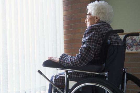 Elderly-woman-in-wheelchair-looking-out-of-window-with-blinds