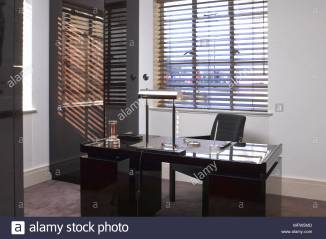 a-modern-home-office-space-with-venetian-blind-covering-the-window-behind-a-black-desk-with-a-lamp-MFW5MD