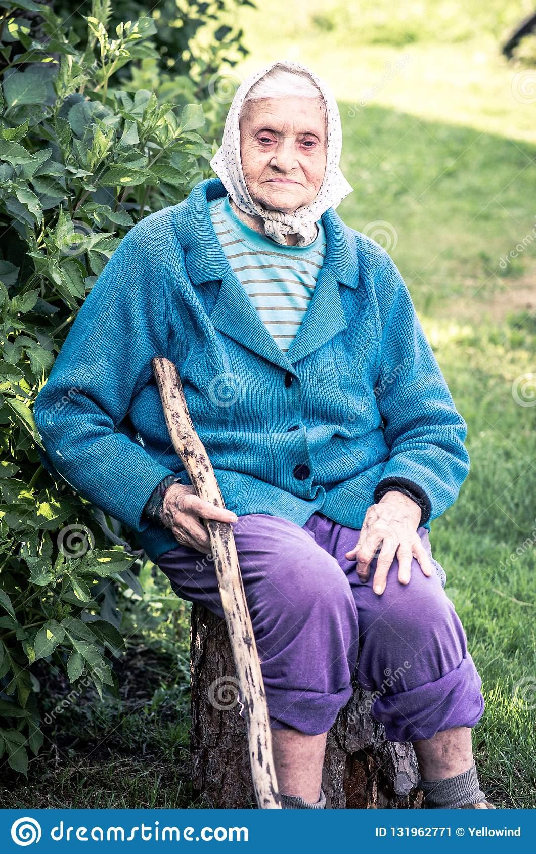 senior-woman-sitting-log-holding-long-cane-senior-woman-sitting-log-holding-long-cane-countryside-village-people-131962771
